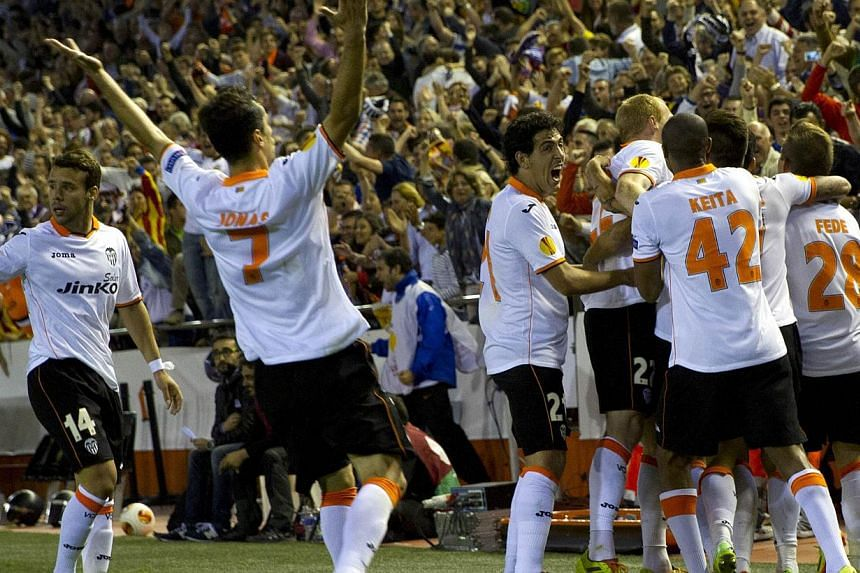 Valencia's players celebrate after scoring their third goal during the UEFA Europa League semi-final second leg football match Valencia CF vs FC Sevilla at the Mestalla stadium in Valencia on May 1, 2014. -- FILE PHOTO: AFP
