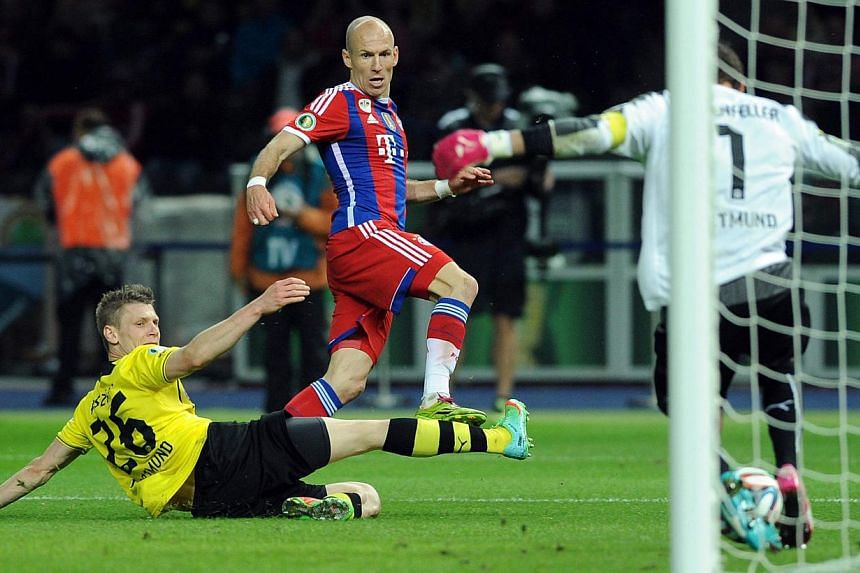 Bayern's Arjen Robben (centre) scores past Dortmund's Lukasz Piszczek (left) and Dortmund goalkeeper Roman Weidenfeller during the German Cup final between Borussia Dortmund and FC Bayern Munich at the Olympic Stadium in Berlin, Germany, on 17 May 20
