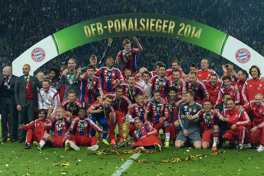 Bayern Munich's players celebrate with the trophy after winning the German Cup final against Borussia Dortmund at the Olympic Stadium in Berlin on May 17, 2014. -- PHOTO: AFP
