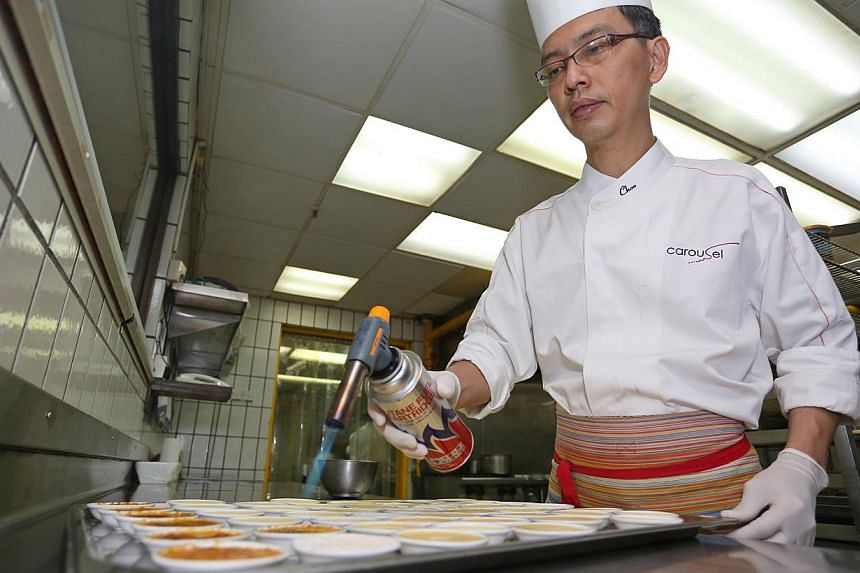 Executive pastry chef Choo Eng Tat from Royal Plaza on Scotts preparing creme brulee. At far left is the safety wall towards which blowtorches are to be pointed at all times. -- PHOTO: EDWARD TEO FOR THE SUNDAY TIMES
