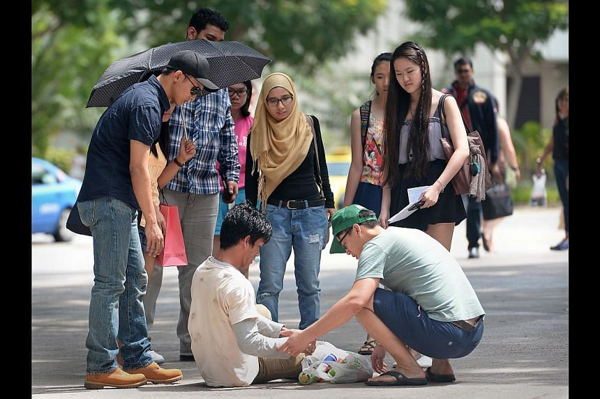Engineer Poh Jing Chieh (above, wearing green cap) and head of business development Samsul Ariffin (far left) helping 21-year-old Ziyad Bagharib after he fell while posing as a beggar for the Hidden Good project. Beautician Cindy Ho (below) giving me