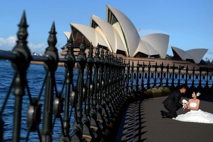 A couple posing for their wedding photo in front of Sydney's iconic Opera House last week. Along with much of south-eastern Australia, the capital of New South Wales is in the midst of an autumn heatwave that is setting records, with daily maximum te