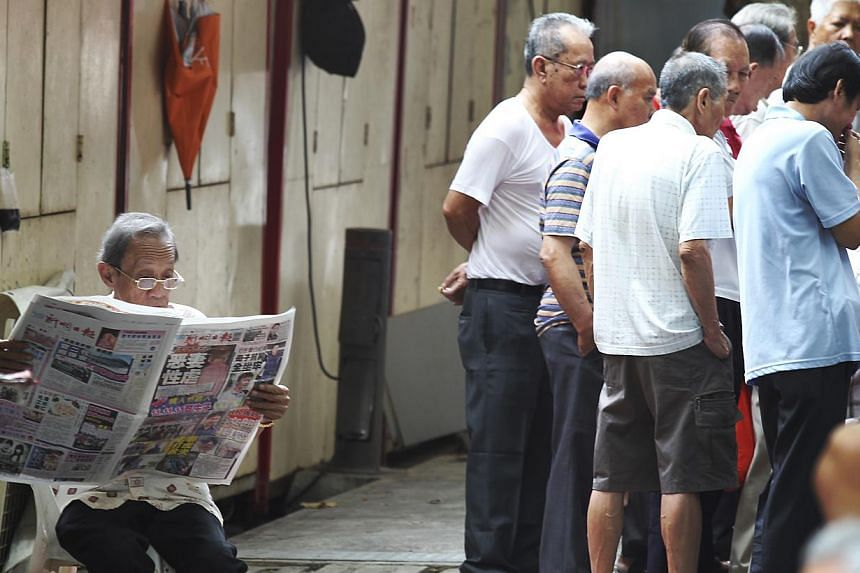 An elderly reading a newspaper while the others watching a game session. -- BT FILE PHOTO: YEN MENG JIN
