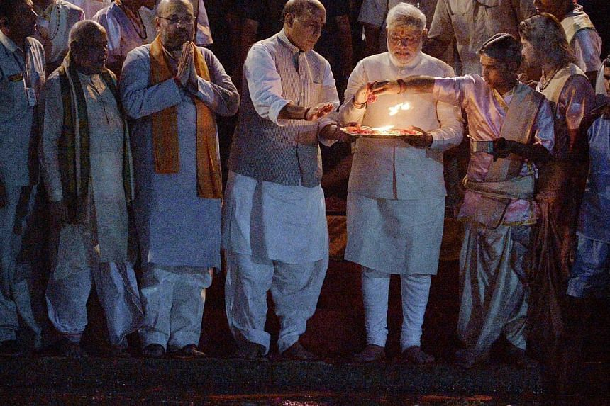 Indian prime minister-elect Narendra Modi, who is holding a tray, performs a religious ritual at the banks of the River Ganges in Varanasi on May 17, 2014. He vows to clean up the holy river Ganges, sacred to millions of Hindus but seeped in fil