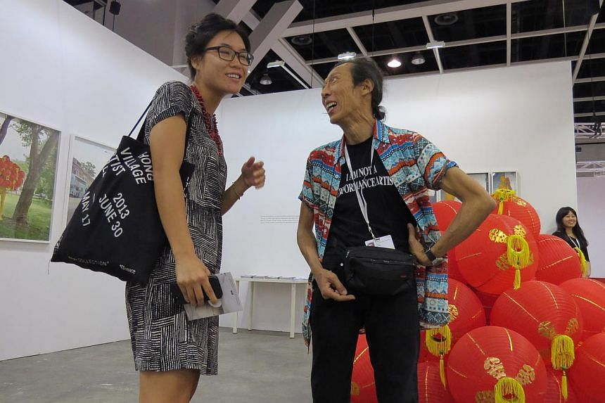 Singapore contemporary artist Lee Wen (right) talking to a visitor at his solo exhibition at the Art Basel Hong Kong. Speculation has been rife on Facebook that the artist was attacked after he expressed concern at an arts forum here about Tiana