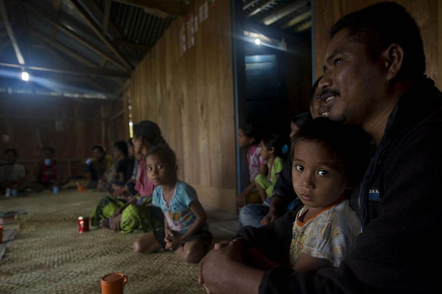 Sumbanese family gather in their house installed with electricity generated from field of small wind turbine in Kamanggih village in Sumba island located in central Indonesia. Until two years ago, most people in Kamanggih village had no power at all,