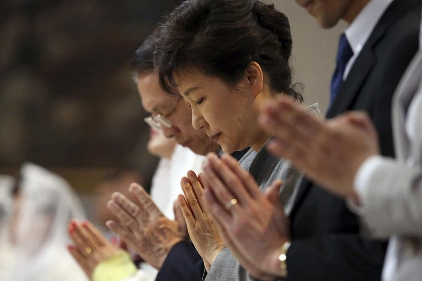 South Korean President Park Geun Hye (centre) prays during a Mass in memory of victims of the sunken Sewol ferry at a Catholic church in Seoul on May 18, 2014. Amid nationwide anger over the incident, Ms Park met relatives of the victims on Friday, r