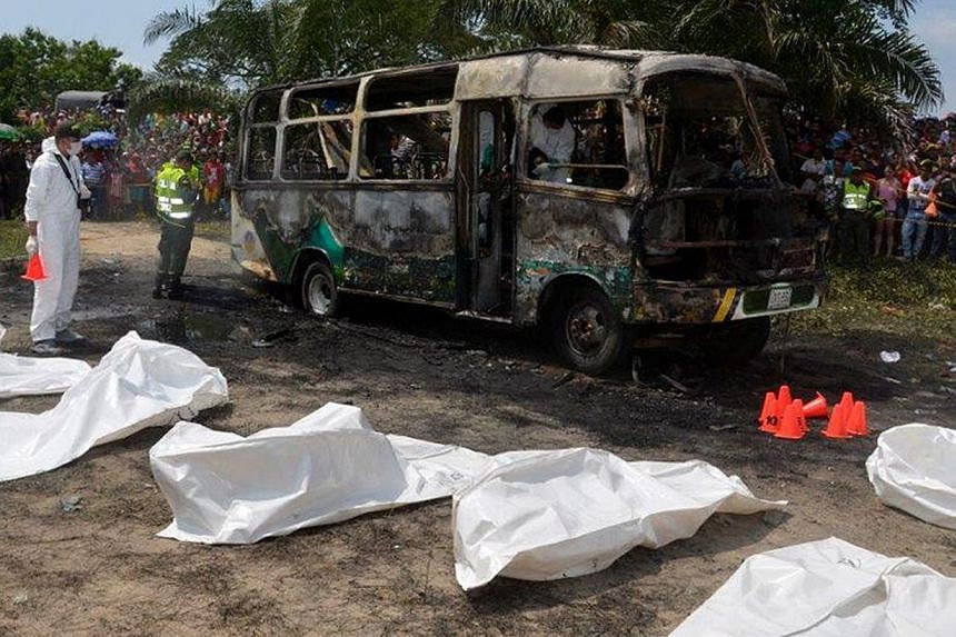 A handout picture provided by the daily El Heraldo shows forensic experts inspecting the site of a burned bus supposedly set on fire due to a mechanic failure, in Fundacion, department of Magdalena, Colombia, 18 May 2014. -- PHOTO: EPA
