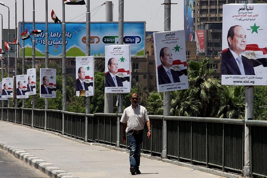 An Egyptian man passes under electoral billboards featuring presidential candidate, Egypt's former defense minister Abdel Fattah al-Sisi in Cairo, Egypt, 18 May 2014. The European Union (EU) said on Monday it would monitor all of Egypt's preside