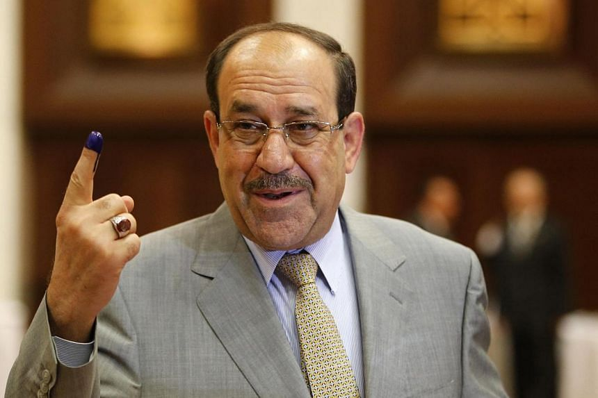 Iraq's Prime Minister Nuri al-Maliki shows his ink marked finger as he votes during parliamentary election in Baghdad April 30, 2014.Prime Minister Nuri al-Maliki's electoral bloc won the most seats in Iraq's parliamentary polls, results releas