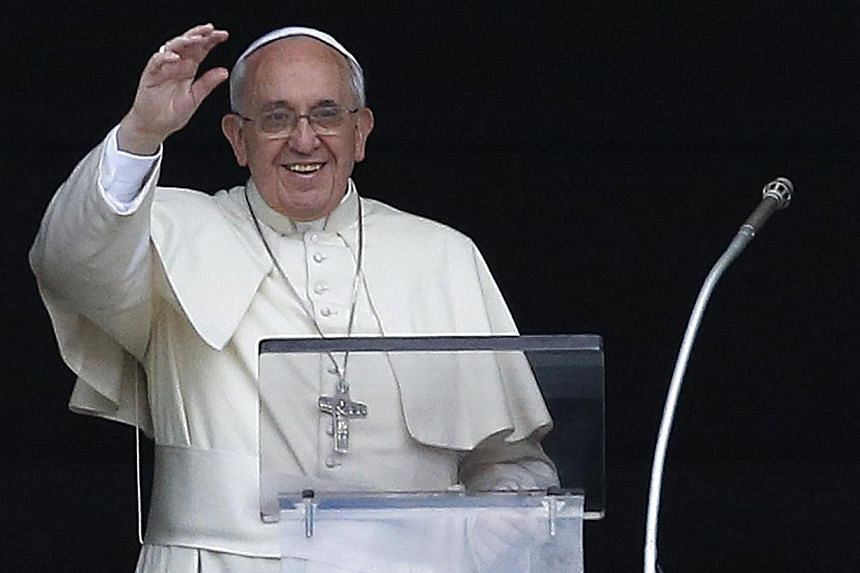 Pope Francis waves as he leads his Sunday Angelus prayer in Saint Peter's square at the Vatican May 18, 2014.Twenty-six women who say they are in love with Roman Catholic priests have written to Pope Francis urging him to make celibacy optional