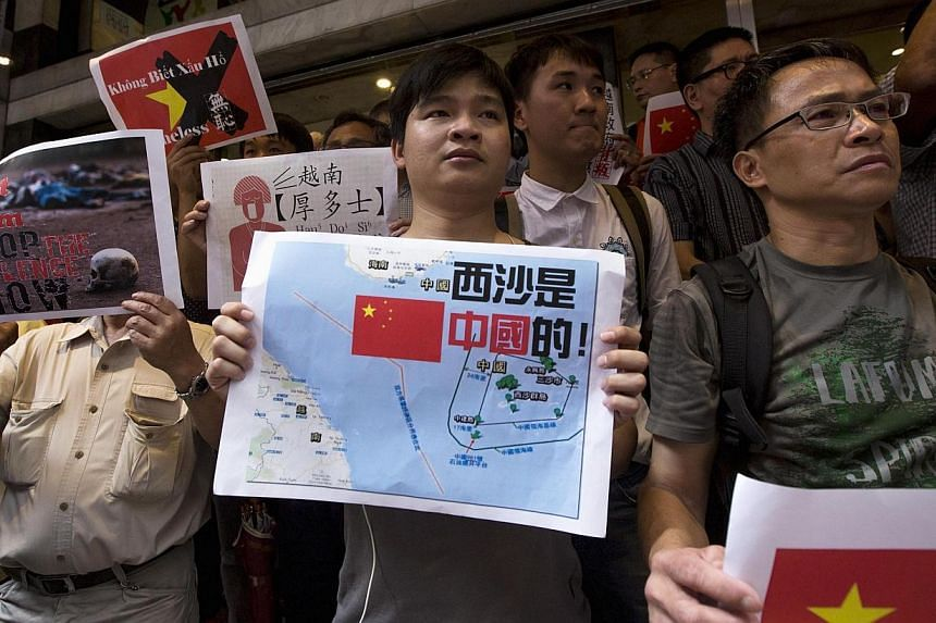 Anti-Vietnam protesters hold posters with slogans and a picture showing a map of the South China Sea including the Paracel Islands, during a protest defending China's territory claim and condemning Vietnam's anti-Chinese protests, in Hong Kong May 19