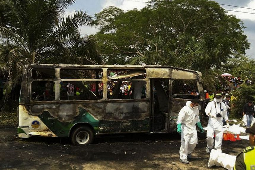 Colombian police stand alongside recovered bodies of children who died in a burned bus in Fundacion, Colombia, on May 18, 2014. -- PHOTO: AFP