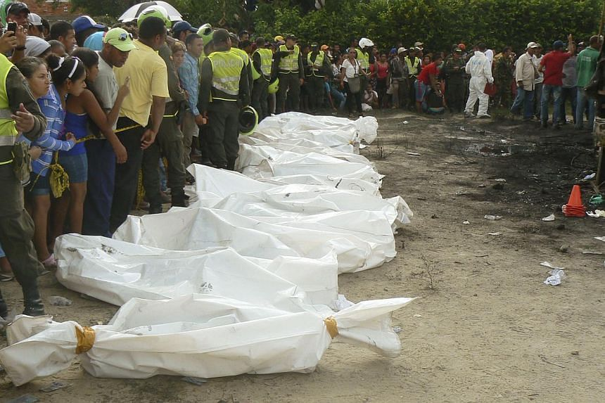 Colombian policemen stand alongside recovered bodies of children who died in a burned bus in Fundacion, northern Colombia, on May 18, 2014. -- PHOTO: REUTERS