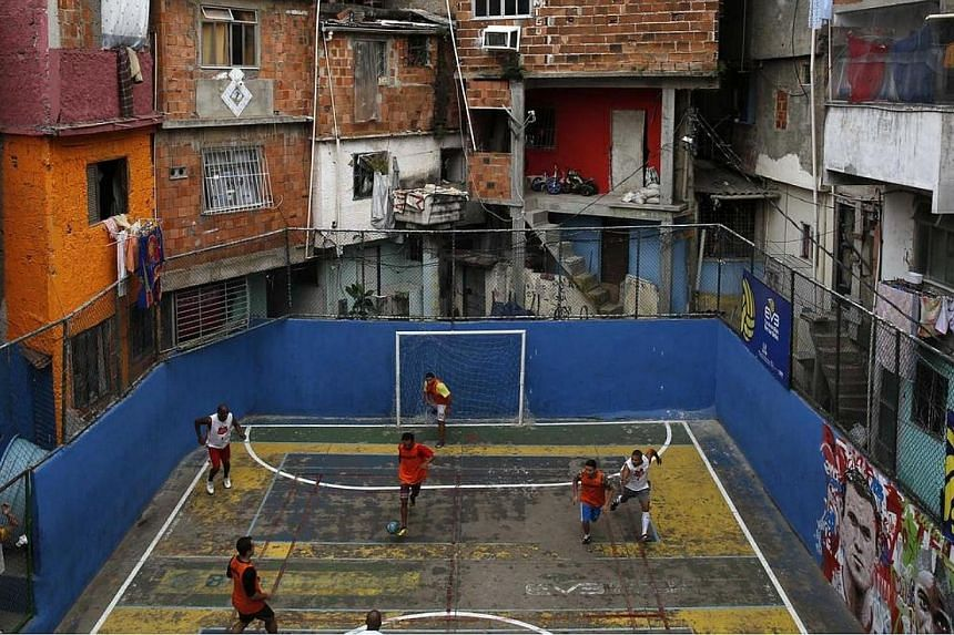 People take part in a soccer match held at the Tavares Bastos slum in Rio de Janeiro on May 18, 2014. The World Cup will be held in 12 cities in Brazil from June 12 till July 13. -- PHOTO: REUTERS
