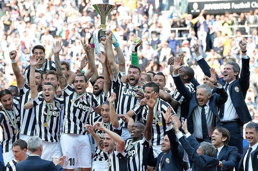 """Juventus' coach Antonio Conte, players and staff celebrate the """"scudetto"""" (Italian championship trophy) at the end of the Italian Serie A football match Juventus FC vs Cagliari Calcio at the Juventus Stadium in Turin, Italy, on May 18 2014. -- PHOTO:"""