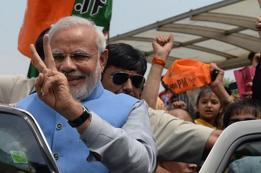 Mr Narendra Modi (in blue) waves as he arrives at Indira Gandhi International Airport in New Delhi on May 17, 2014. -- FILE PHOTO: AFP