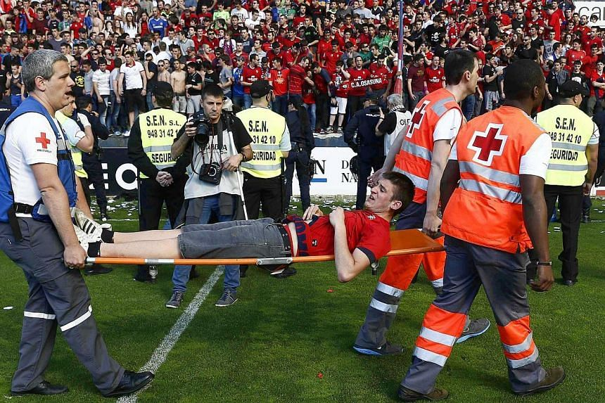 An injured supporter (centre) is stretchered off by medical staff after a railing collapsed during the Spanish Primera Division soccer match between CA Osasuna and Real Betis at the El Sadar stadium in Pamplona, northern Spain, on 18 May 2014. Severa