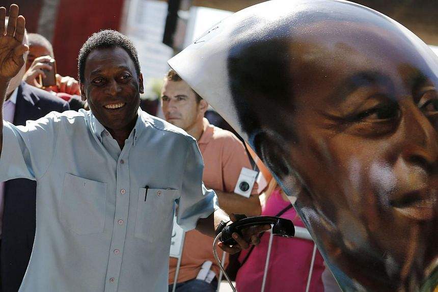 Brazilian football legend Pele waves next to a public telephone booth with an image of his face painted by Brazilian artist Ciprus after he autographed it, during the Call Parade art exhibition in Sao Paulo on May 8, 2014. -- FILE PHOTO: REUTERS
