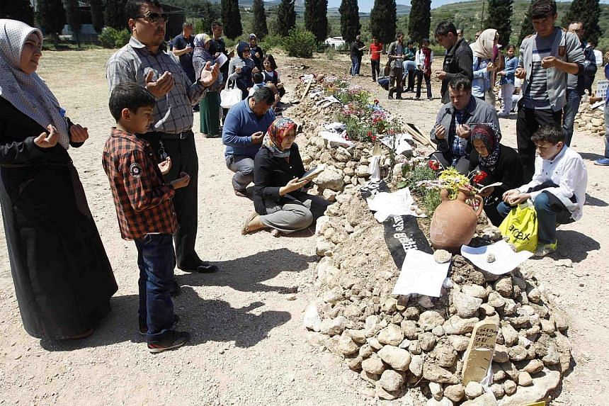 People mourn at graves for miners who died in Tuesday's mine disaster, at a cemetery in Soma, a district in Turkey's western province of Manisa on May 18, 2014. -- PHOTO: REUTERS
