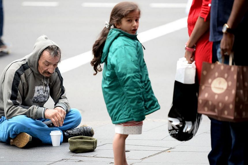 This photo taken on May 12, 2014 shows a homeless man sitting on a street in Sydney. Australian Prime Minister Tony Abbott has suffered a voter backlash after a budget described as the worst in 20 years with two polls Monday showing support for