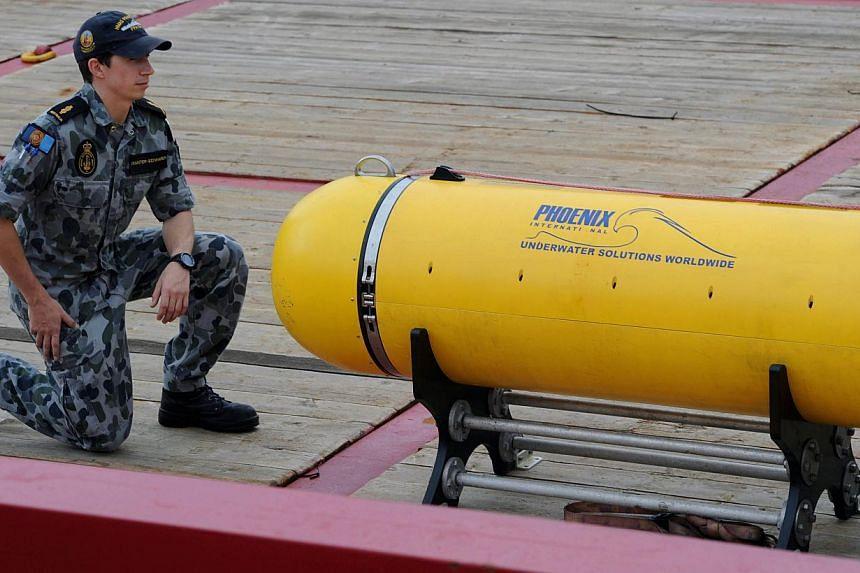 Able Seaman Matthew Tranter-Edwards (left) kneels alongside the Phoenix Autonomous Underwater Vehicle 'Artemis' Bluefin-21, on the deck of the Australian navy ship Ocean Shield, berthed at Fleet Base West near Perth on May 5, 2014, as it replenis