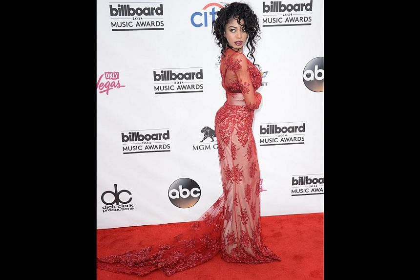 Singer Dencia's attempt at lace and fish tail doesn't work as well - the red dress disappears into the carpet and her rat's nest hair-do and blood-red lips tips the outfit over into trashy rather than classy. -- PHOTO: AFP
