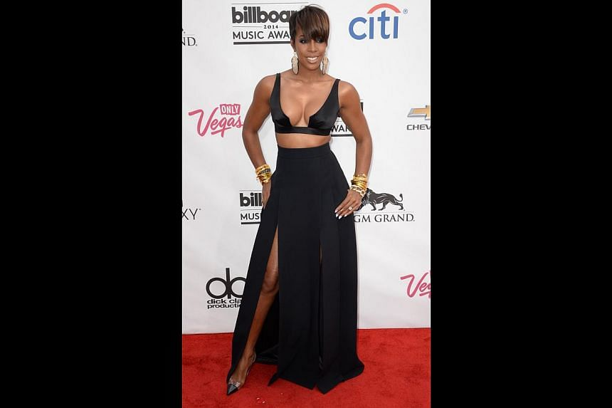 Kelly Rowland demonstrates the wonders of fashion tape in her precariously-tiny bra-top teamed with a slinky skirt with a thigh-high slit.-- PHOTO: AFP