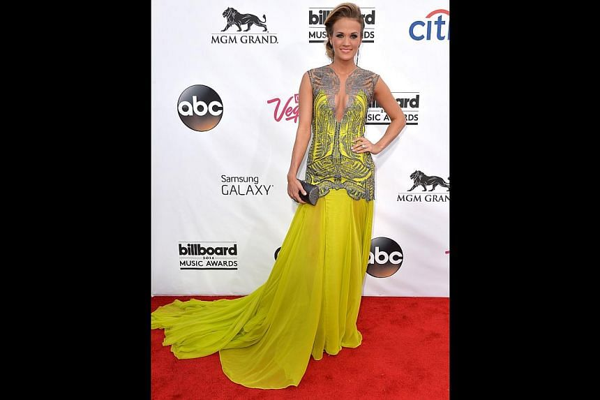 Carrie Underwood pops in her bright yellow Oriett Domenech gown with sequinned embellishments.-- PHOTO: AFP