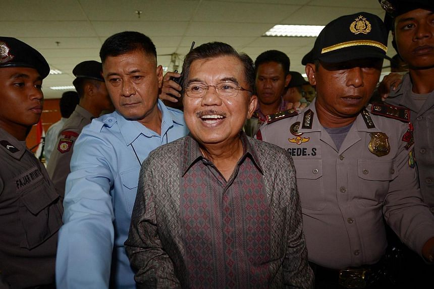 Former Indonesian vice president Jusuf Kalla (centre) leaves the Indonesia's Corruption Court in Jakarta on May 8, 2014. -- FILE PHOTO: AFP