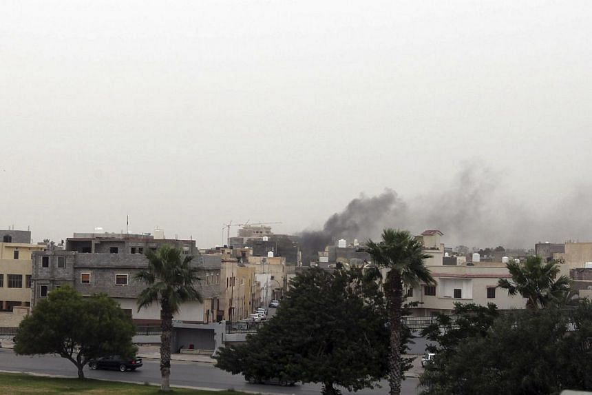 Smoke rises over the General National Congress building in Tripoli on May 18, 2014. -- PHOTO: REUTERS
