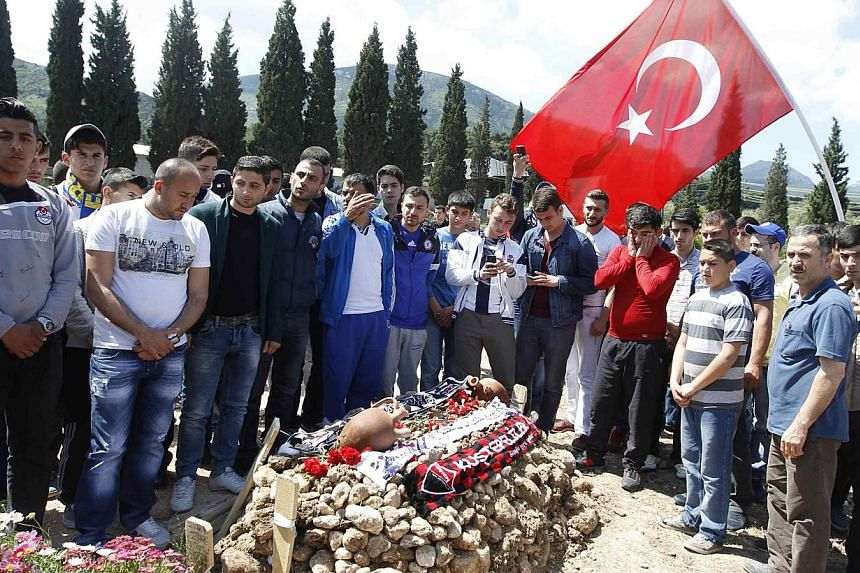 People mourn at graves for miners who died in Tuesday's mine disaster, at a cemetery in Soma, a district in Turkey's western province of Manisa on May 18, 2014.Two more officials in Turkey have been charged with manslaughter as the government p