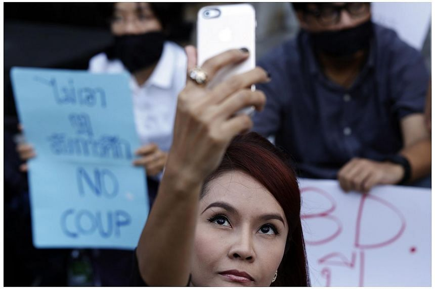 "A woman takes a ""selfie"" photograph as activists attend a small protest against the declaration of martial law and the army's involvement in politics, in central Bangkok, on May 20, 2014. -- PHOTO: REUTERS"