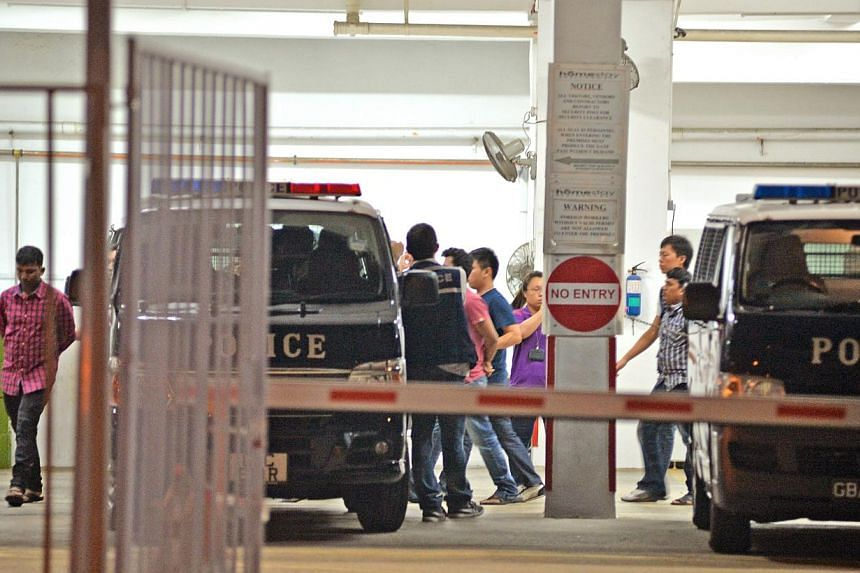 Police arrest 35 foreign workers involved in a fight at Homestay Residences at Kaki Bukit Avenue 3 on March 25, 2014. Eight Bangladeshi workers have been cleared of the dormitory riot - which is thought to have erupted over the result of a cricket ma