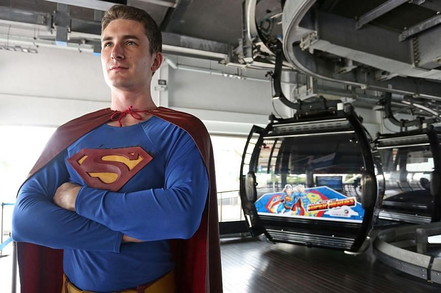 Superman poses for a photograph with a superman-decorated cable car in the background. From the end of May, visitors riding the cable cars between Mount Faber and Sentosa can fly with their favourite superheroes and take a selfie with them.-- S