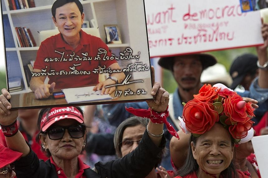 """Thai pro-government """"Red Shirts"""" holds a portrait of fugitive former premier Thaksin Shinawatra during a rally at Phutthamonthon suburb of Bangkok on April 5, 2014.Thailand's ousted prime minister Thaksin Shinawatra, a hugely controversial figu"""