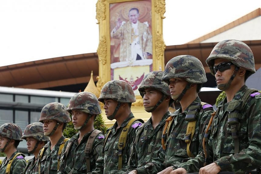 Thai soldiers next to portrait of King Bhumibol Adulyadej after the declaration of martial law at the Army Club in Bangkok, Thailand, 20 May 2014.Thailand's army chief said rival political groups should talk to each other and that the martial l