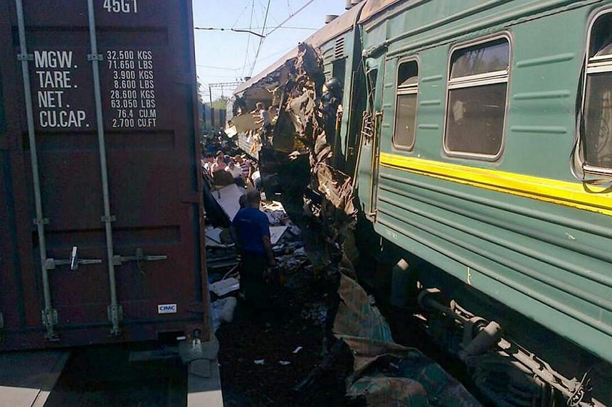 A handout photo provided on May 20, 2014, by the Russian Emergencies Ministry's Moscow Regional Centre shows the site of a collision of freight and passenger trains at the Bekasovo railway station, about 80 km (50 miles) south of Moscow. A freig