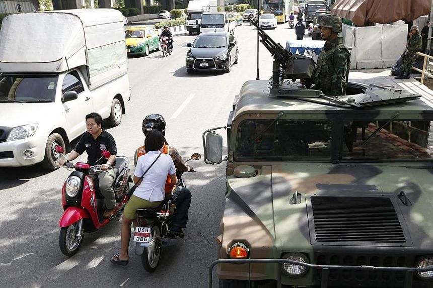 Motorists on their way as Thai soldiers take to the streets with a heavy machine gun on a Humvee military vehicle at a main road outside the Royal Thai Police Sports Club in Bangkok, Thailand on May 20, 2014.The Philippines on Tuesday, May 20,
