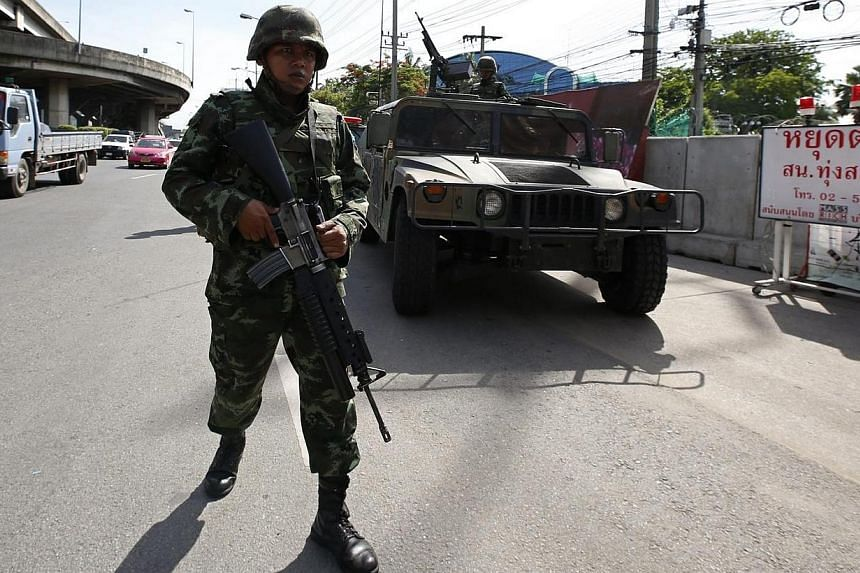 Thai soldiers on patrol after the declaration of martial law at a main road outside the Royal Thai Police Sports Club in Bangkok, Thailand on May 20, 2014.Thai mainstream media on Tuesday, May 20, 2014, greeted the imposition of martial law and