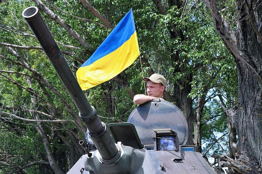 A Ukrainian soldier stands guard on an armoured personnel carrier on the road from Izyum to Slavyansk on May 20, 2014.Ukraine confirmed on Tuesday, May 20, 2014, that Russia had pulled its troops back from the border for the first time in a mov