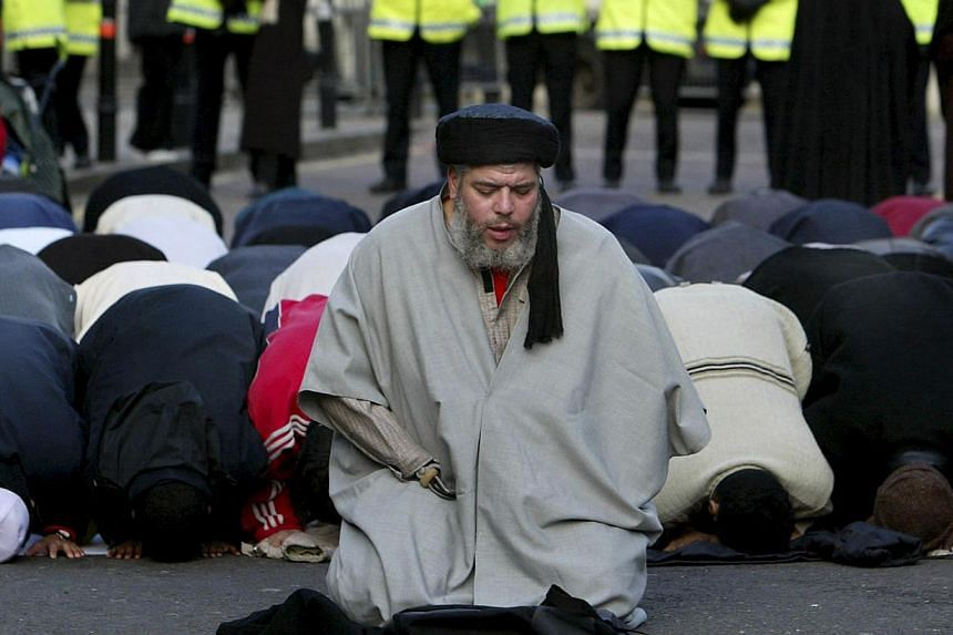 Muslim cleric, Abu Hamza al-Masri, is seen leading prayers outside the North London Central Mosque, in Finsbury Park, north London in this January 24, 2003 file photograph. -- PHOTO: REUTERS