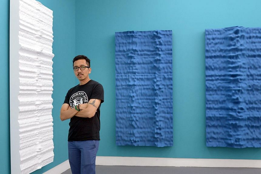 New and old in solo show: Singapore artist Jeremy Sharma with his paintings (from left) Parkes, Tahata and Ubuntu. -- ST PHOTO: LIM SIN THAI