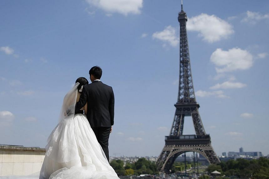 A wedding couple of tourists pose for their own photographer at the Trocadero Square near the Eiffel Tower in Paris on May 16, 2014. People tend to choose spouses who have similar DNA, according to scientists who reported on Monday, May 19, 2014, the