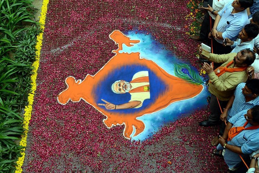 In this photograph taken on May 16, 2014, Indian supporters of the Bharatiya Janata Party (BJP) look on near a rangoli decoration bearing the image of BJP prime ministerial candidate Narendra Modi and the map of India at Shri Kamalam, the BJP Gujarat