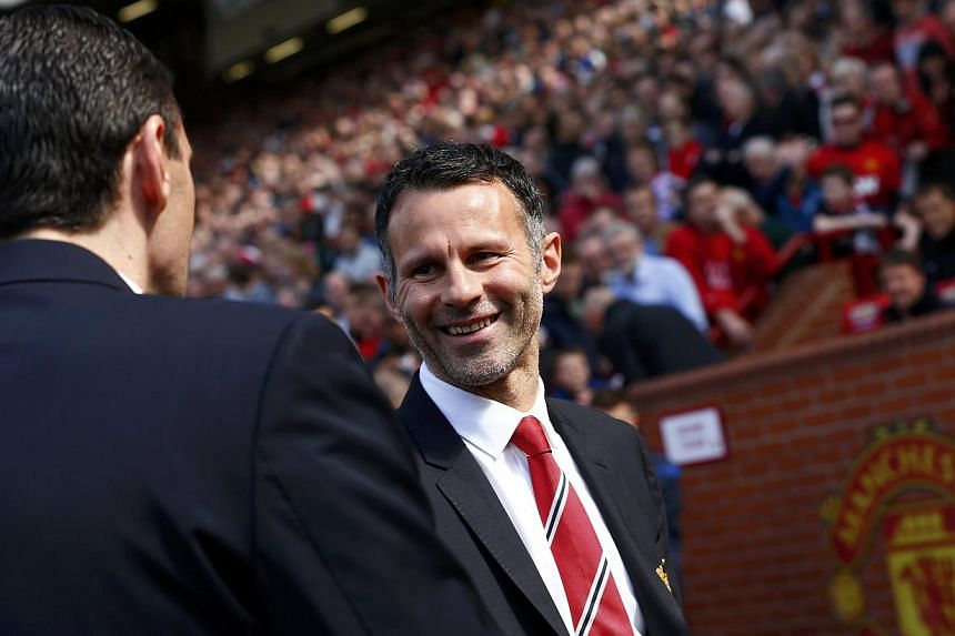 Manchester United caretaker player manager Ryan Giggs (right) greets Sunderland manager Gus Poyet before their English Premier League football match at Old Trafford in Manchester, May 3, 2014. -- FILE PHOTO: REUTERS