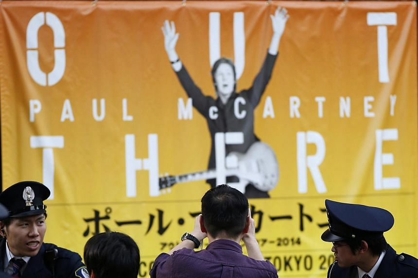 A fan takes a photo of a banner of singer Paul McCartney after the cancellation of McCartney's concert at the National Stadium in Tokyo May 18, 2014. Former Beatle Paul McCartney has cancelled his Japan tour due to illness, organisers said on Tu