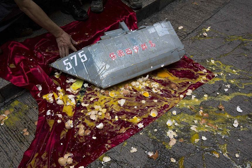 An anti-Vietnam protester picks up a model of Chinese People's Liberation Army Navy (PLAN) Type 054A Frigate FFG-575 Yueyang on a Vietnamese flag, as eggs are thrown by anti-Vietnam protesters, during a protest defending China's territory claim and c
