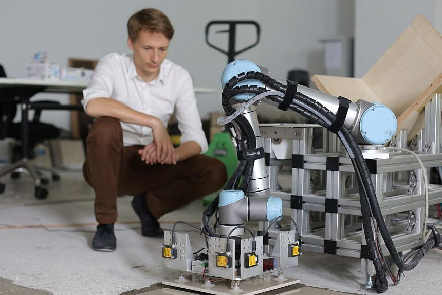 Tobias Bonwetsch, a team member that worked on the prototype, looks on as he gives demonstrates the capabilities of the robotic tiling machine. -- ST FILE PHOTO: ONG WEE JIN