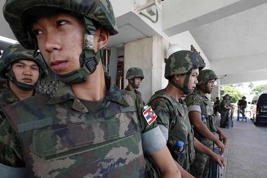 Thai soldiers stand ready at the doors of Thai Parliament as anti-government protesters rally outside in a call for a final battle, in Bangkok, Thailand, on May 9, 2014. -- PHOTO: EPA